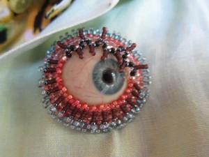 Andrea Hartman turns prosthesis glass eye into artful brooch.